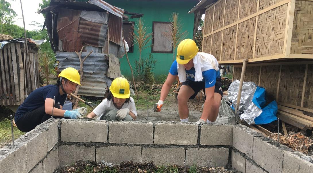 Tre volontärer bygger en toalett under deras volontärresa utomlands.